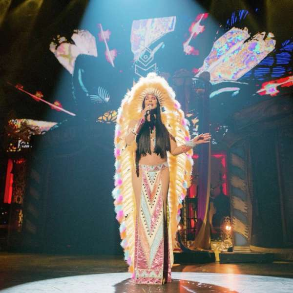 Smaller image of Cher performing solo with yellow headdress.