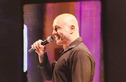 Joa Rogan on stage holding a microphone.