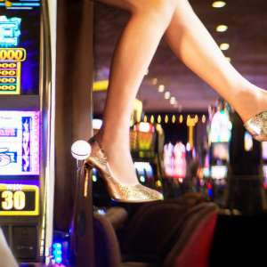 A lady wearing gold heels sitting on the slot machine.