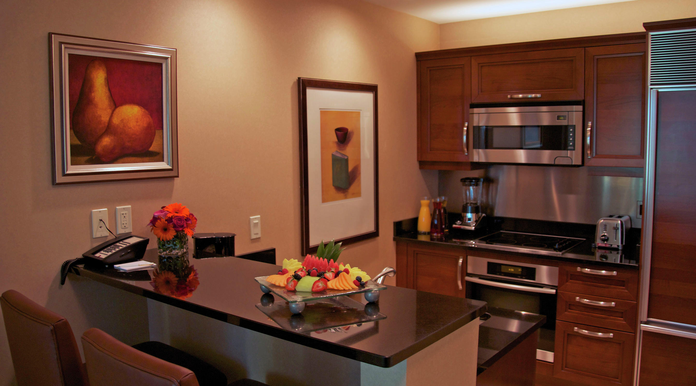 Signature Two Bedroom Balcony Suite Kitchenette with Fruit and Flowers