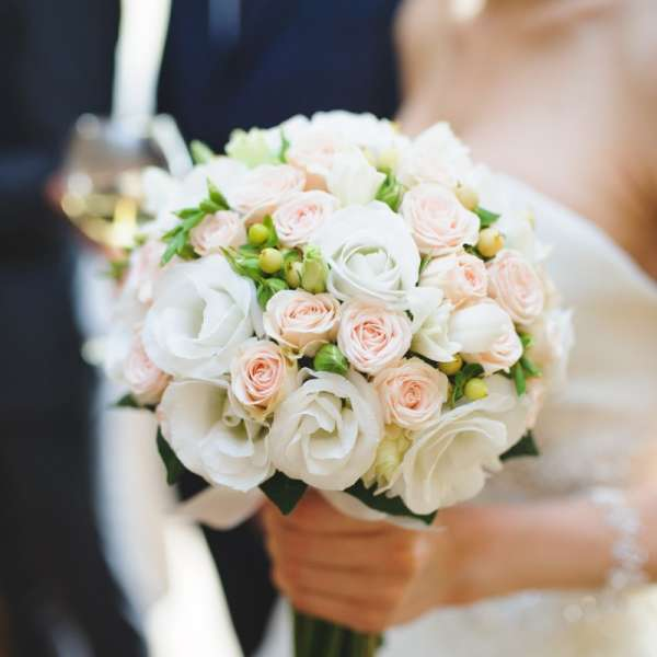 A bride holding a bouquet of roses standing next to the groom.