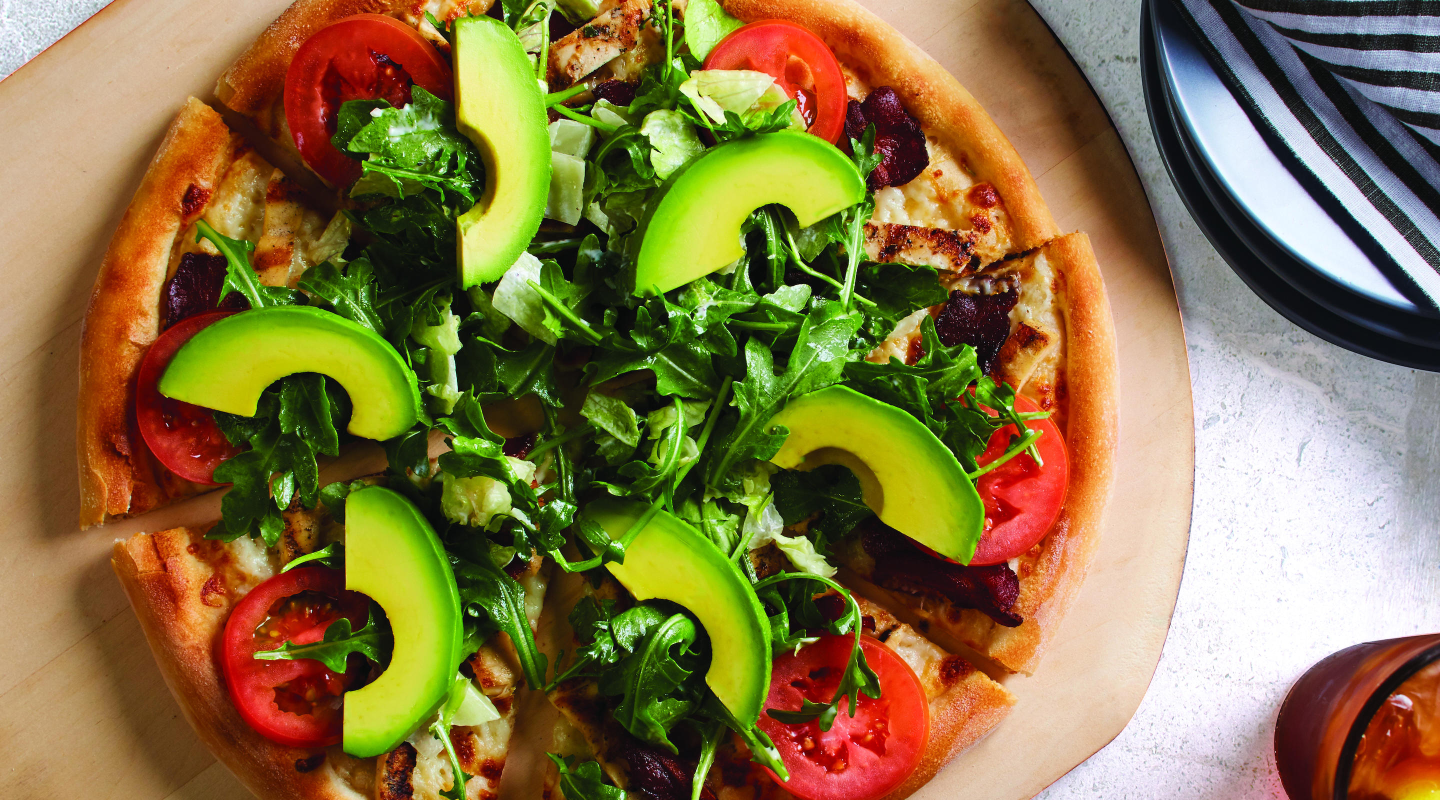 California Club pizza, with Nueske's applewood smoked bacon, roasted chicken and Mozzarella,  topped with avocado, wild arugula, fresh torn basil and romaine lettuce.
