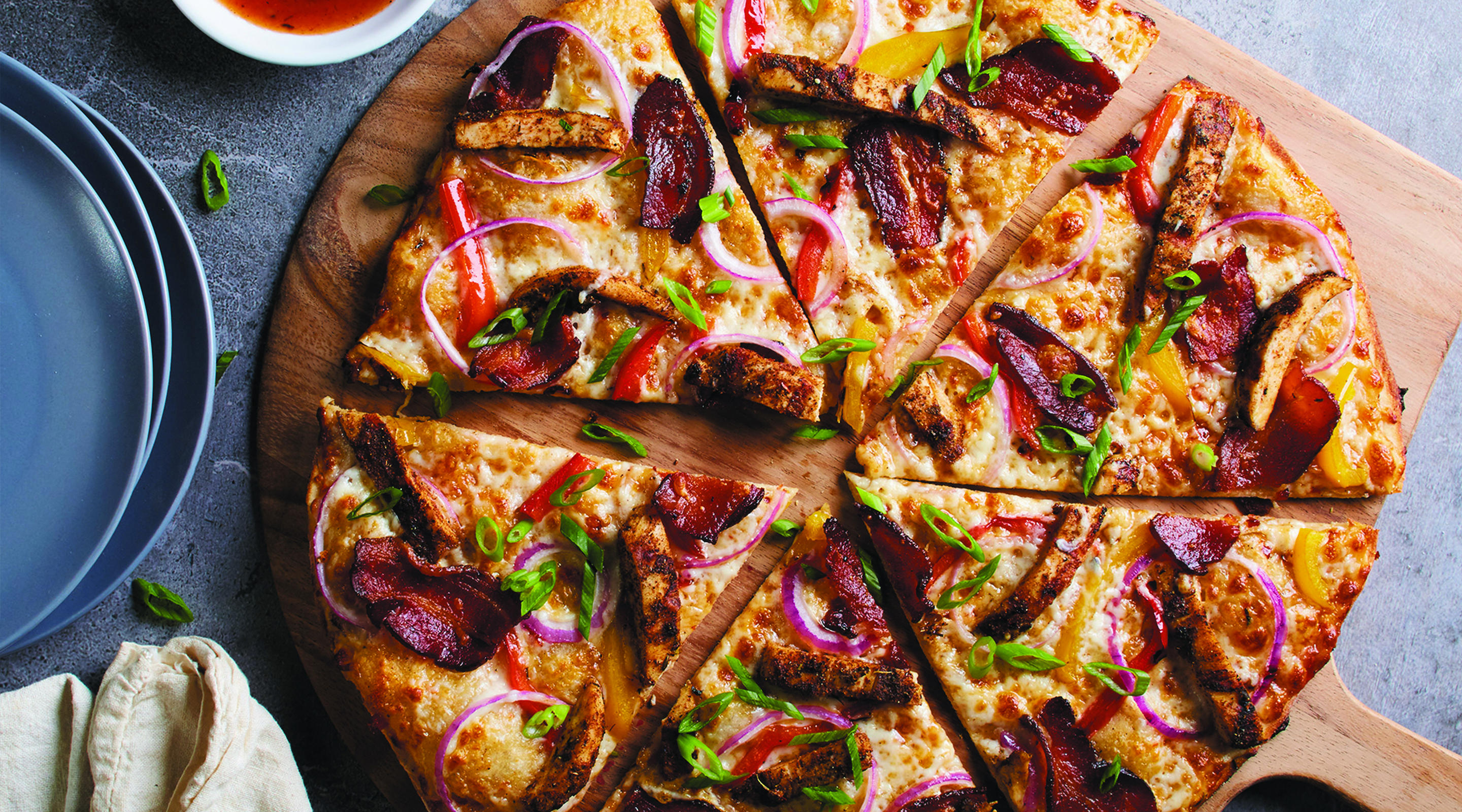 Jamaican Jerk Chicken Pizza, with spicy sweet Caribbean sauce, authentic Jamaican spices, Nueske's applewood smoked bacon, red onions and bell peppers.
