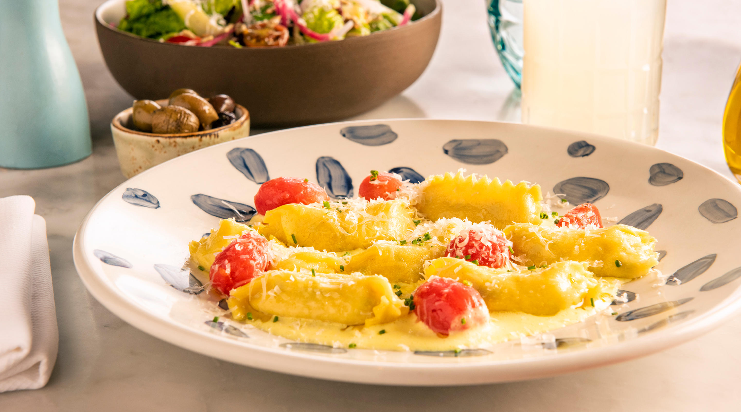 A plate of homemade agnolotti and a salad.