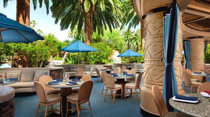Unwind in a tropical poolside setting while enjoying the serene sounds of the waterfall and savoring classic dishes at Paradise Cafe