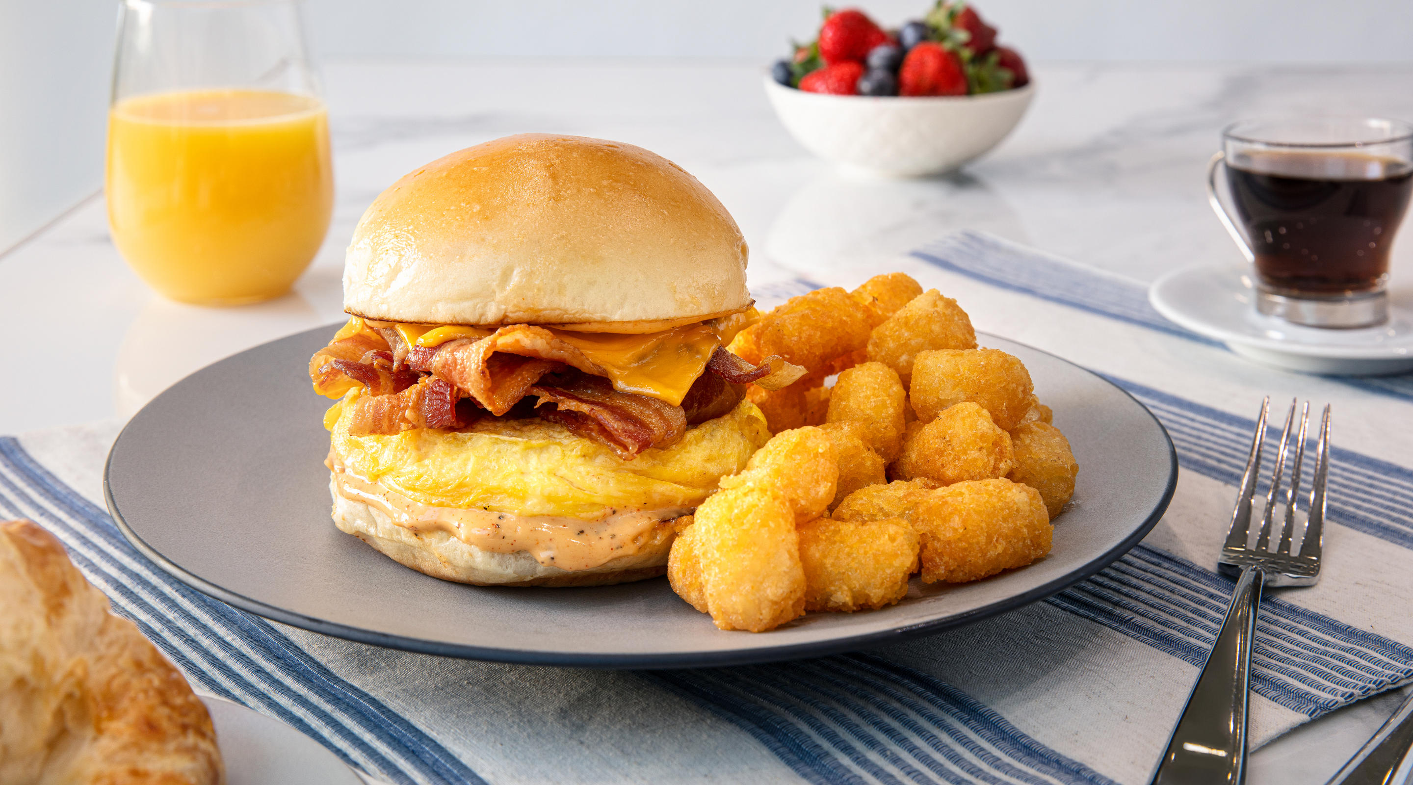 Bacon, egg and cheese breakfast sandwich with tater tots.