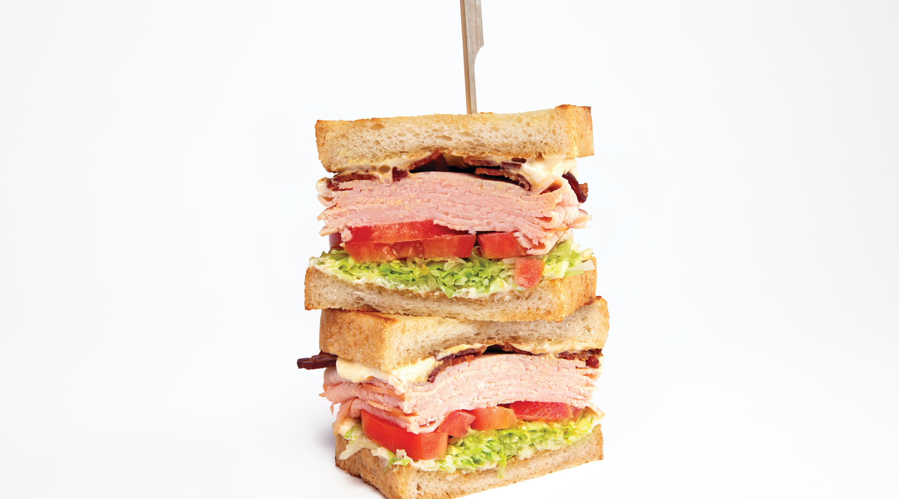 A stacked turkey club sandwich from Snacks at Mirage.
