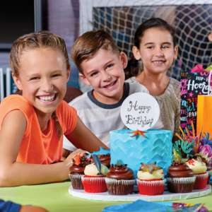 Kids enjoying a birthday celebration at a decorated table.