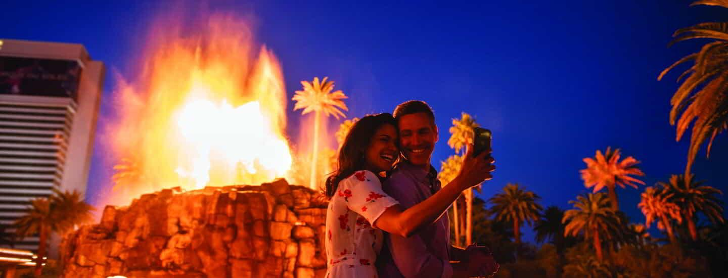 A couple taking a selfie in front of the Mirage Volcano.