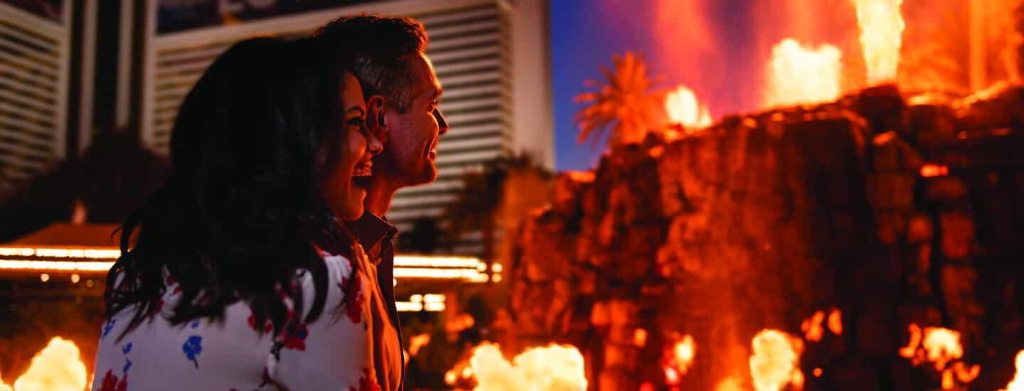 A couple watching the Mirage Volcano at night.