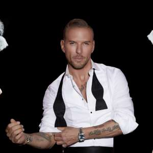 Image of Matt Goss flanked by two showgirls.