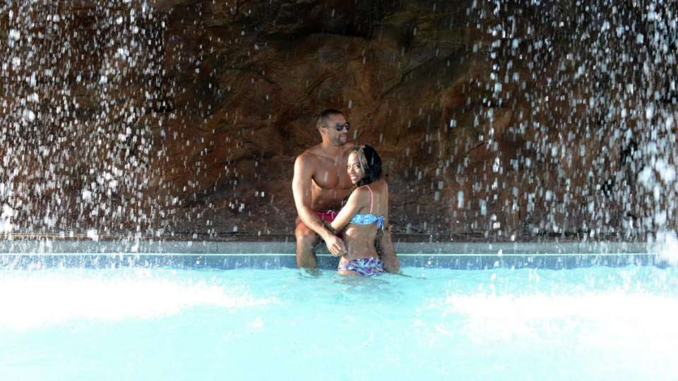 Couple under the waterfall at The Mirage pool