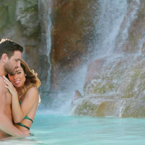 mirage-pool-lifestyle-genx-couple-waterfall-hug