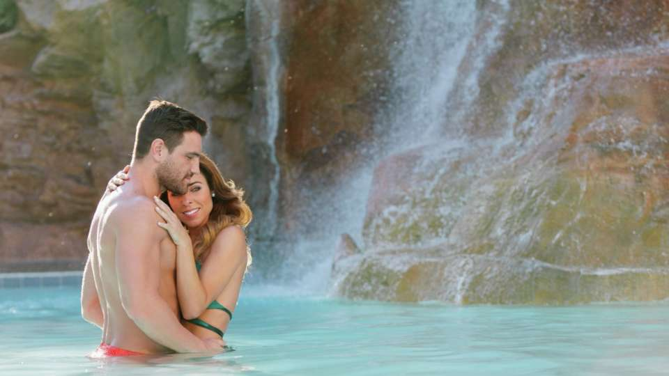 Couple hugging by the waterfall in The Mirage pool