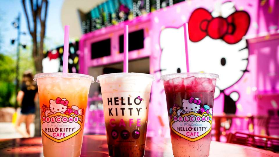 Three Hello Kitty Cafe beverages with the background of T Mobile Arena.