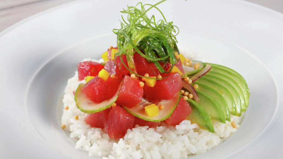 Our Poke Bowl features fresh Tuna, Sweet Onion, Seaweed Salad, Daikon,  and Cucumber on a bed of hot Sushi Rice.